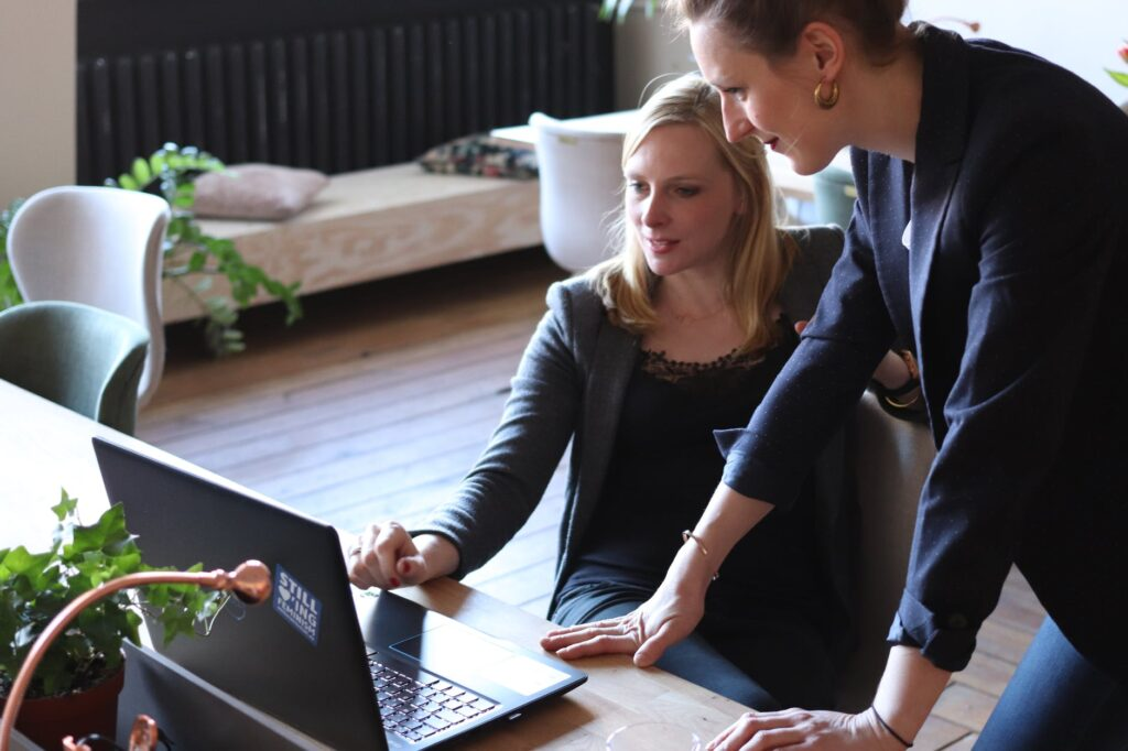 two women using on black laptop computer